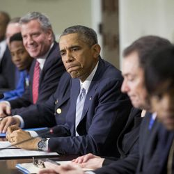 President Barack Obama, center, pauses as he speaks during his meeting with elected officials, law enforcement officials and community and faith leaders in the Old Executive Office Building on the White House Complex in Washington, Monday, Dec. 1, 2014. Obama says that in the wake of the shooting of an unarmed 18-year-old man in Ferguson, Mo., he wants to make sure to build better trust between police and the communities they serve. To the left of Obama is New York Mayor Bill de Blasio.