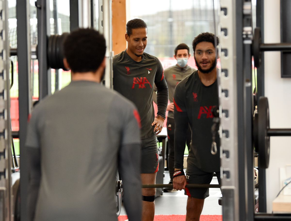"""Van Dijk """"assists"""" Gomez, who works at the squat rack, as the two work their way back to fitness."""