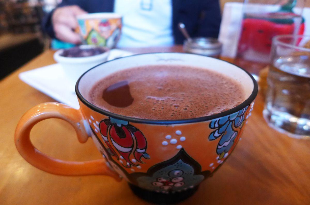 An orange ceramic cup with foamy chocolate inside.