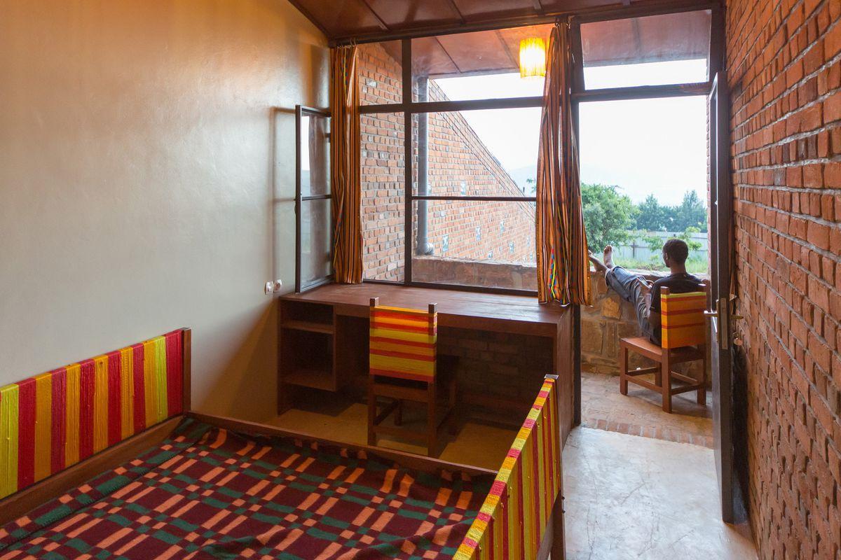 Man sitting in a share house in Rwanda.