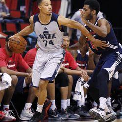 Utah Jazz's Jared Cunningham drives around Washington Wizards' Scott Suggs during the first half of their NBA summer league basketball game Wednesday, July 15, 2015, in Las Vegas. (AP Photo/John Locher)