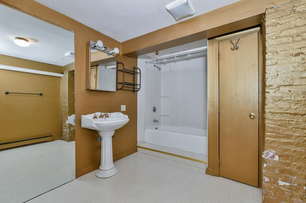 A bathroom with a standing sink, a tub without a curtain, a narrow closet door, and there's no toilet visible.