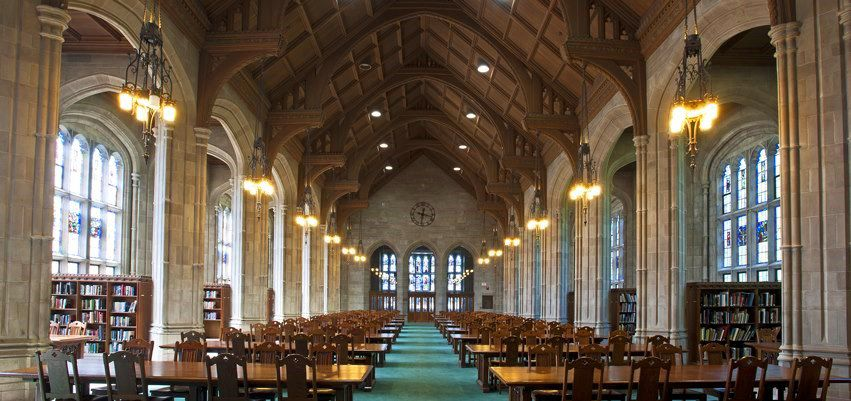 A cavernous library with an arched roof and rows of tables and chairs.