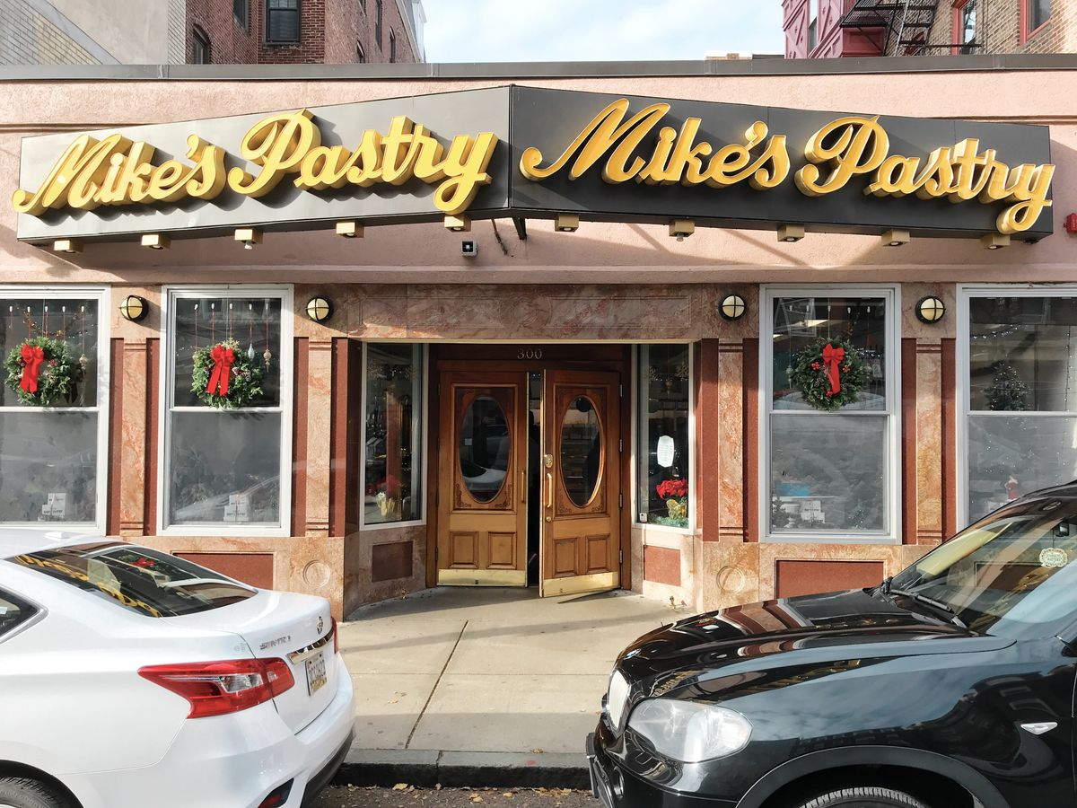 """The exterior of Mike's Pastry's North End location features a large gray sign above the entrance with """"Mike's Pastry"""" written twice in yellow cursive"""