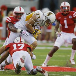 Wyoming wide receiver Dominic Rufran (33) is tackled by Nebraska safety Corey Cooper, left, and Nebraska cornerback Ciante Evans (17), with Nebraska safety Harvey Jackson (1) looking on, in the first half of an NCAA college football game in Lincoln, Neb., Saturday, Aug. 31, 2013. (AP Photo/Nati Harnik)