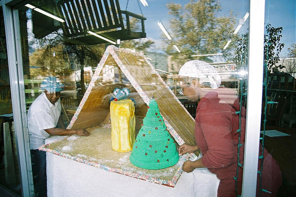 """Mary, left, and Nada Meeks put the final touches on their holiday window display, """"Who Moved My Cheese,"""" at D&B Woods."""