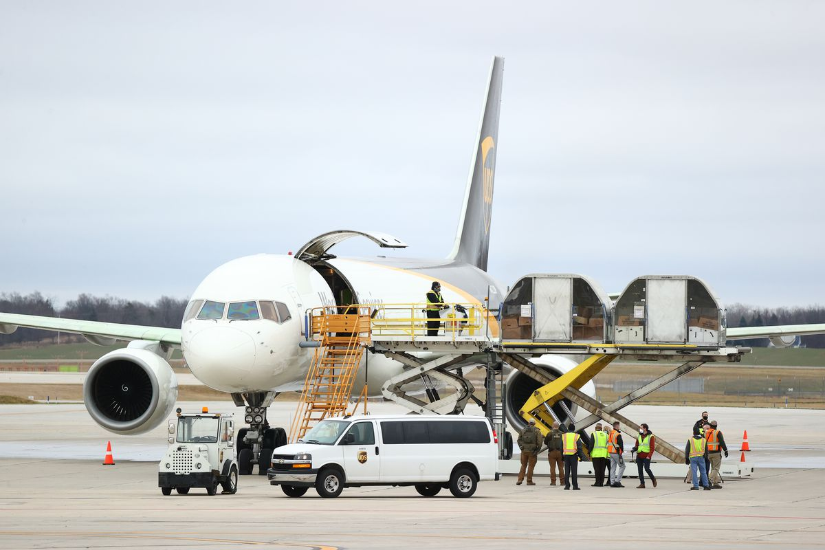 Workers in neon green load a hydraulic platform next to a white cargo plane with boxes containing the vaccine.