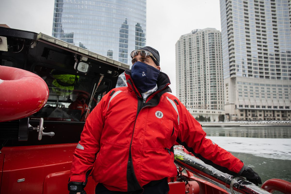 """Jason Lach, Chicago Fire Department's deputy district chief in charge of marine and dive operations, wears a jacket that doubles as a flotation device while standing on the """"Christopher Wheatley"""" Thursday afternoon as the vessel breaks ice that formed on the Chicago River."""