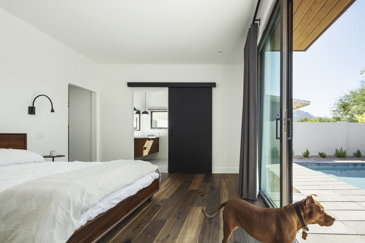 A bright bedroom has glass doors that open out to the pool.