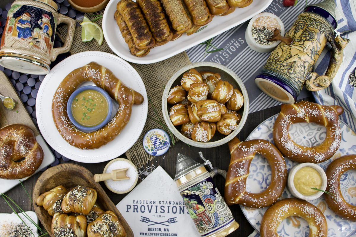 Overhead view of an Oktoberfest-themed selection of several shapes of soft pretzels, dipping sauces, and salts, accompanied by several decorated beer steins