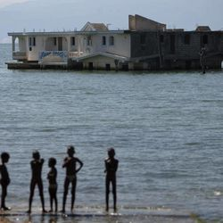 In this Sept. 6, 2012 photo, children stand on the shores of Lake Azuei near a submerged hotel in Thomazeau, Haiti, near the border with the Dominican Republic. The waters' rise has worsened exponentially in recent years, especially after heavy rains in 2007 and 2008 hit the island of Hispaniola. Tropical Storm Isaac dumped more water on the region last month, sparking more damage.