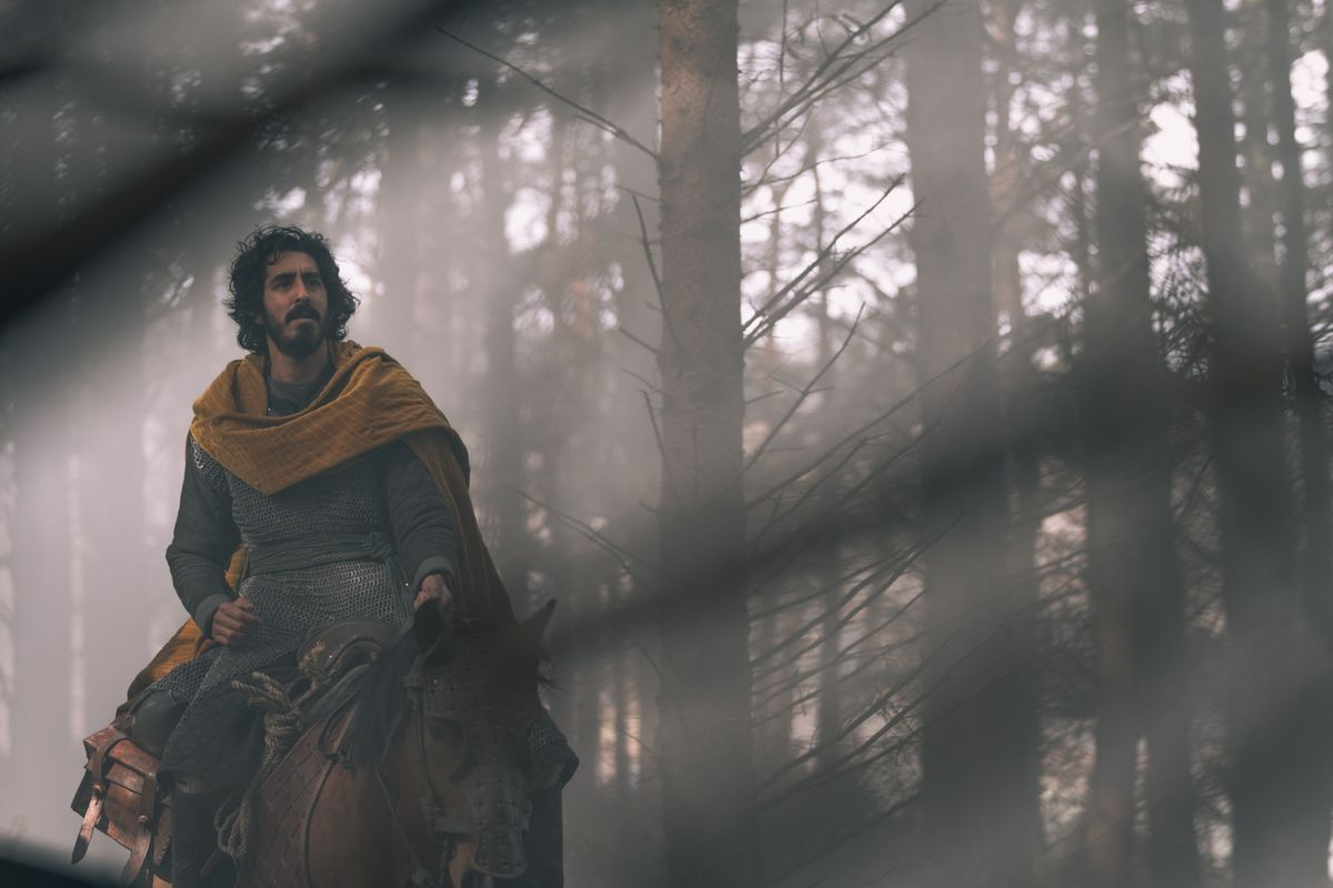 Gawain sits on a horse in the woods.