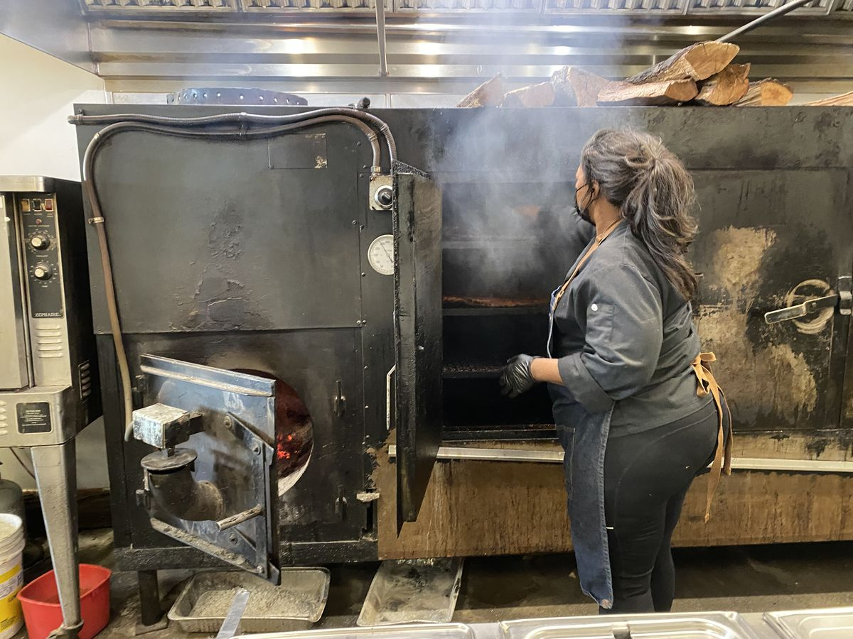 A female pitmaster opening a large door for a smoker to check ribs.