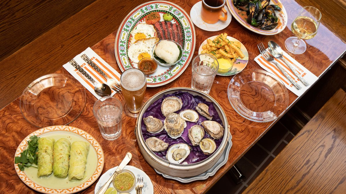 A wooden table featuring several different plates of food including mussels, sunnyside up eggs and bacon, and open-faced oysters