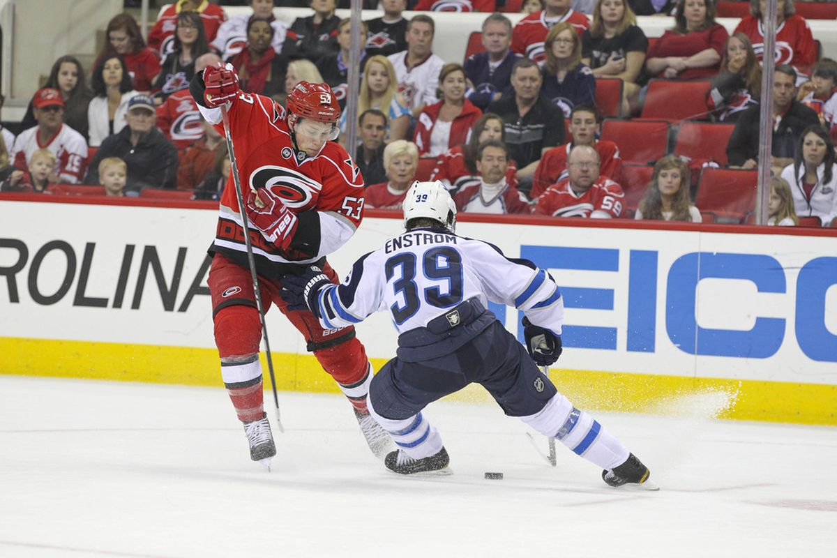 March 30, 2012; Raleigh, NC, USA; Carolina Hurricanes center Jeff Skinner (53) tries to carry the puck by the Winnipeg Jets defensemen Tobias Enstrom (39) during the 2nd period at the PNC center. Mandatory Credit: James Guillory-US PRESSWIRE