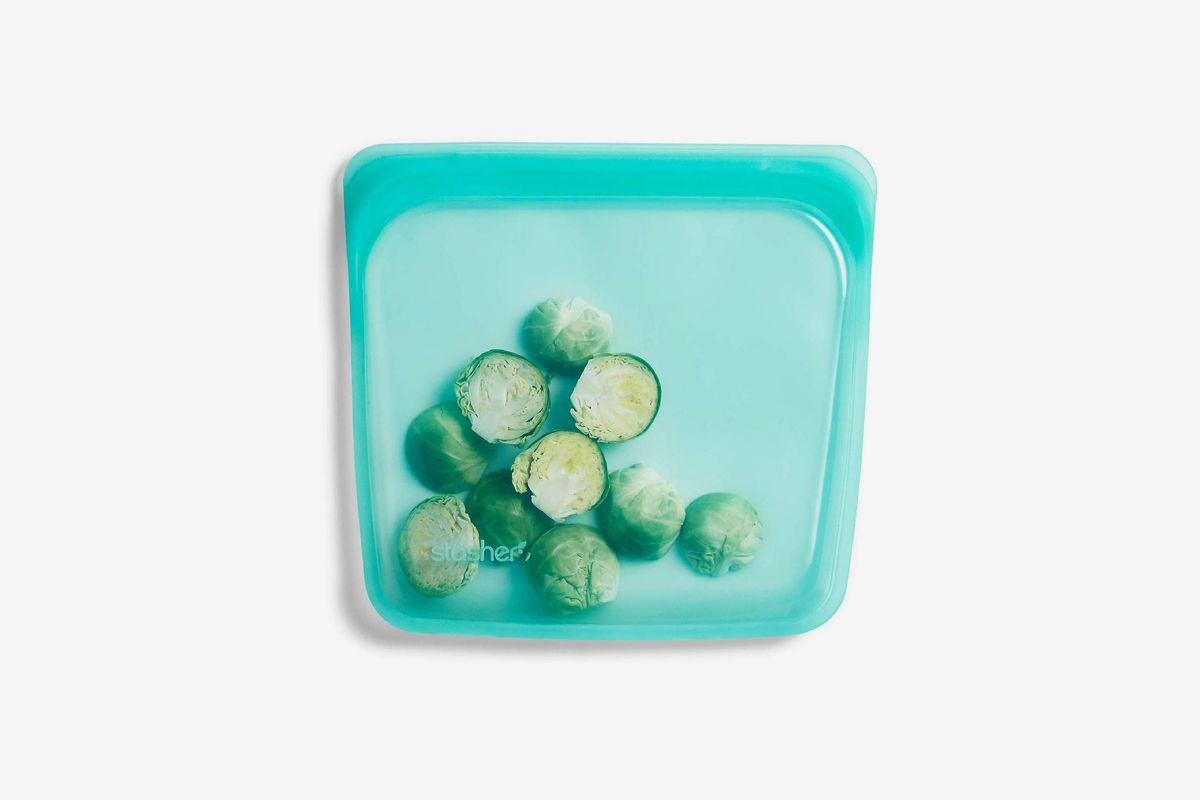 A blue silicone reusable sandwich bag filled with brussels sprouts