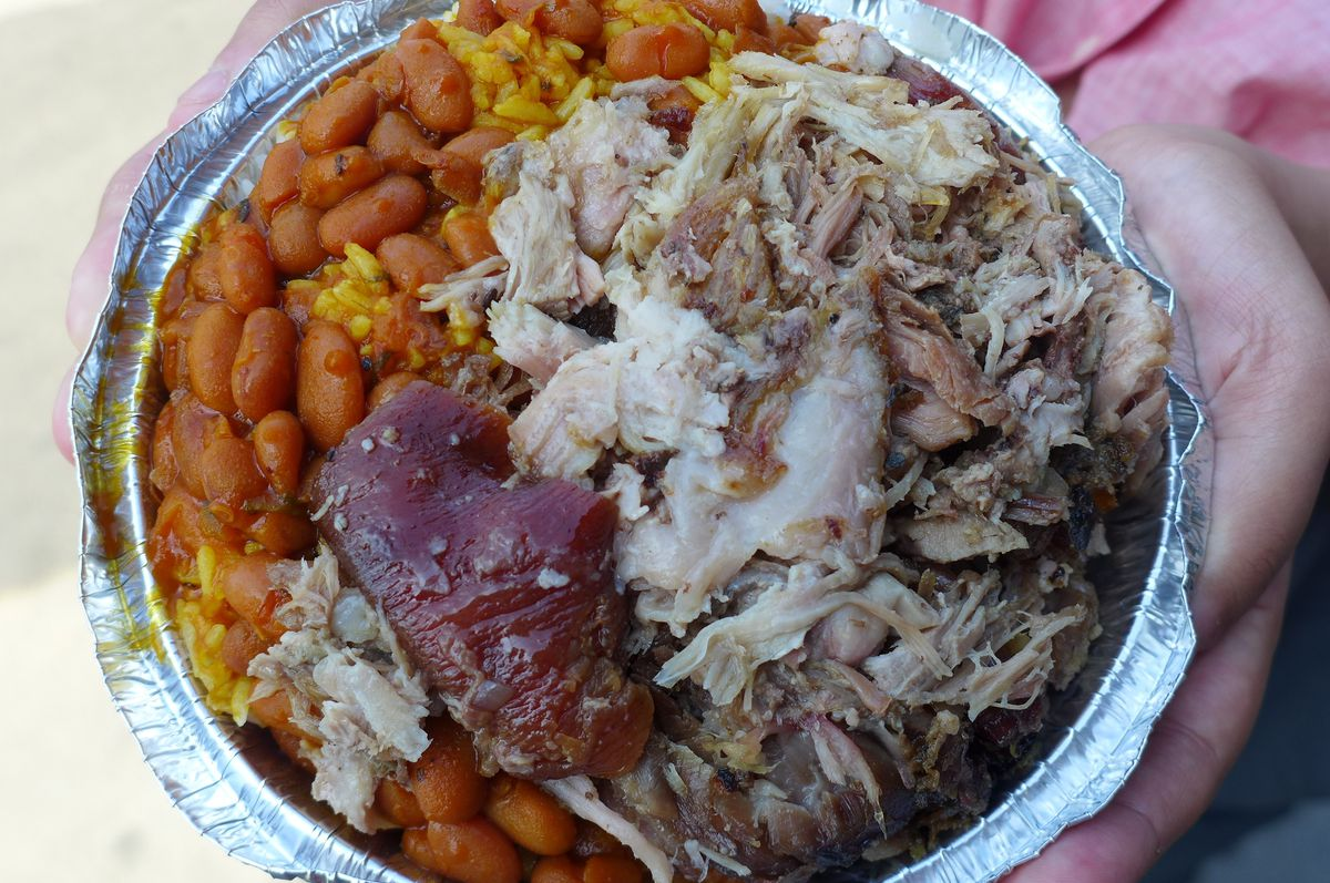 A round aluminum container of pork and brown skin, brown beans, and yellowish rice packed in tight.