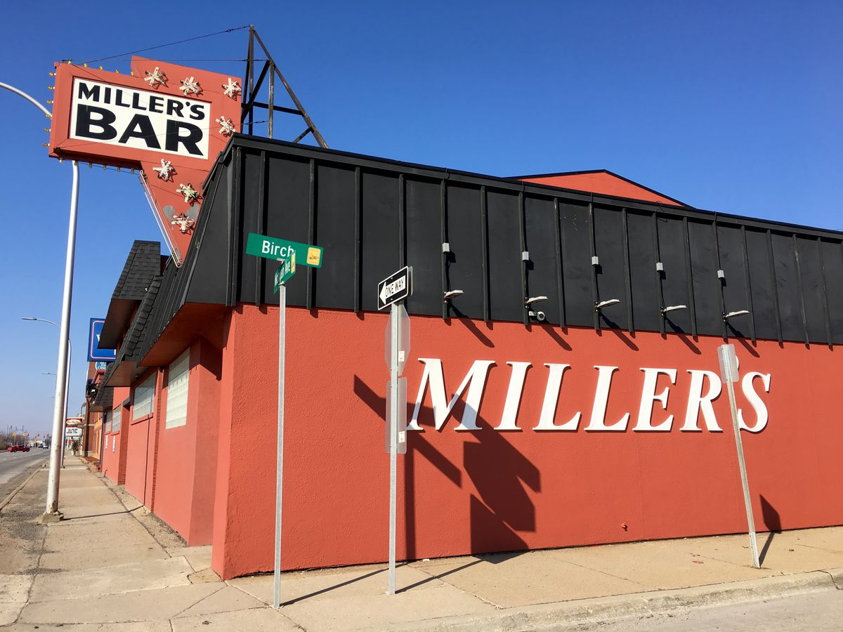 A Miller Bar's red building features a sign surrounded by neon starbursts on a sunny, cloudless day.