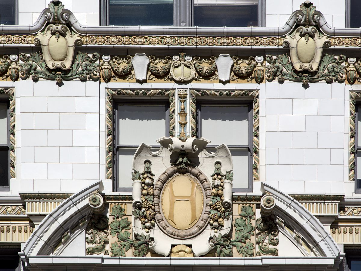 The exterior of a building in San Francisco. The facade has elaborate designs around the entrance and along the front of the building.