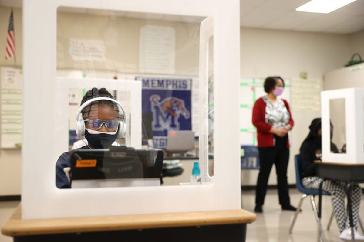 A fifth grade girl wearing a mask works on a laptop behind a clear desktop barrier. A woman stands in the background near another girl working at a desk behind a partition.