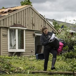 Jamie Kasper takes supplies out of her home on Evergreen Lane near Chestnut Avenue in Woodridge after a tornado ripped through the western suburbs overnight, Monday morning, June 21, 2021.