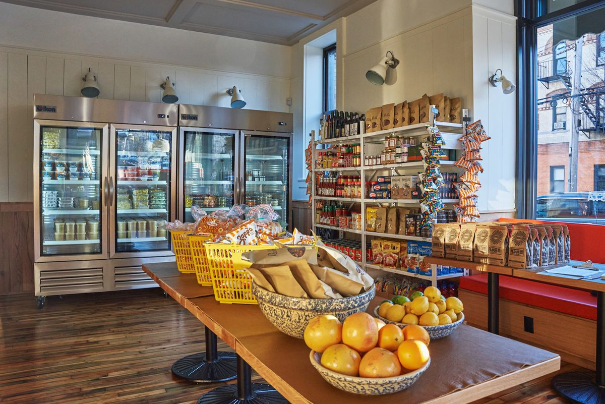The interior of a restaurant that's setup as a market place with fridges full of items and tables with fruit and pasta