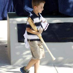 Cooper Stone walks past an unveiled statue with a jersey, bat and ball signed by Buddy Bell during the Fan Statue dedication on Thursday, April 5, 2012, in Arlington, Texas. The statue is of Rangers fan Shannon Stone, who died after falling out of the stands trying to catch a ball in 2011, and his son Cooper.