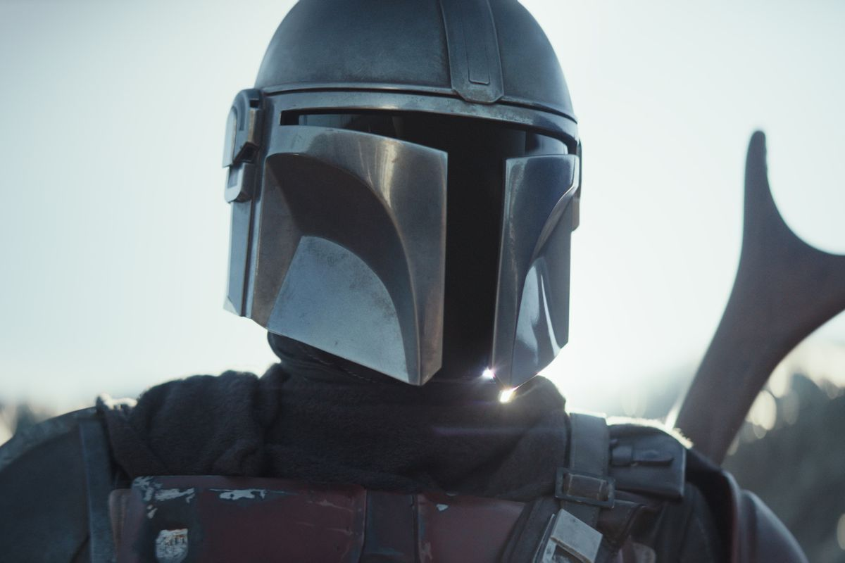 the mandalorian in tight close-up with a shiny helmet and gun sticking out of frame