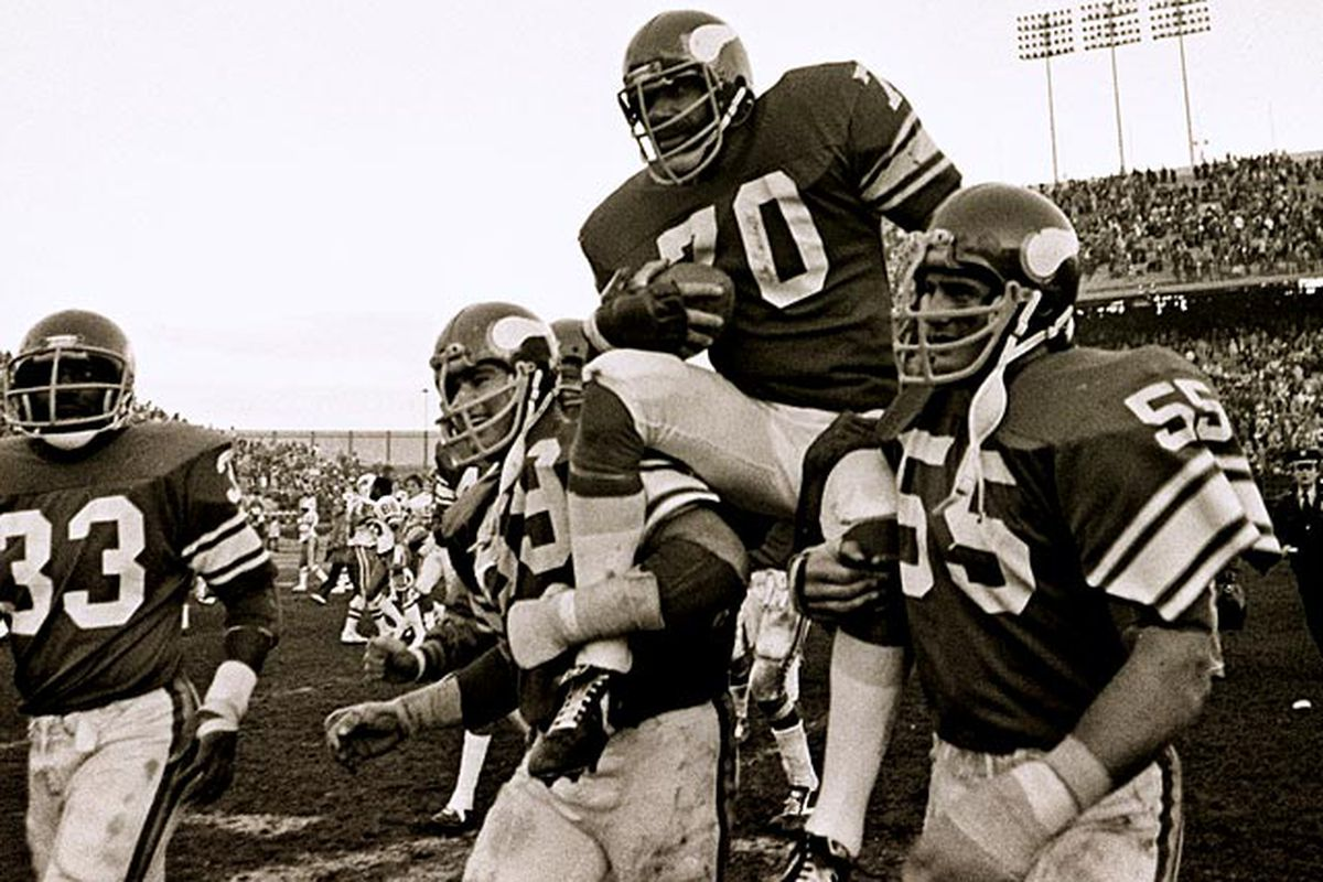 Jim Marshall is carrried off the field by Doug Sutherland (69) and Scott Studwell (55) after his last game in 1979. Brent McClanahan (33) looks on.