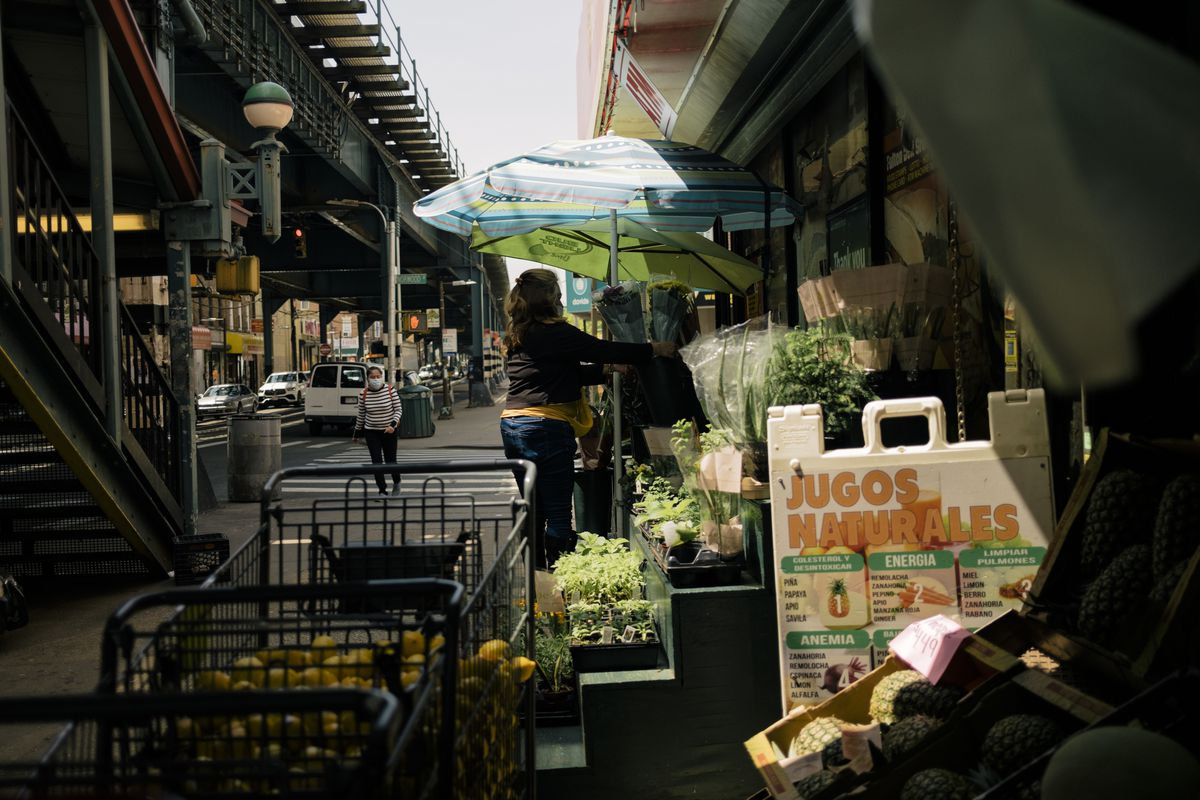 A market in Cypress Hills has fresh fruits and vegetables outside. A woman looks at the wares while another woman walks down the street.