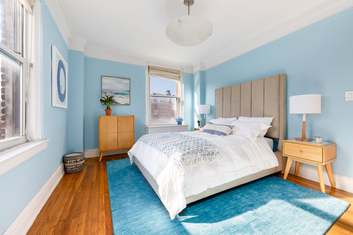 A bedroom with a light blue wall, hardwood floors, and a medium-sized bed.