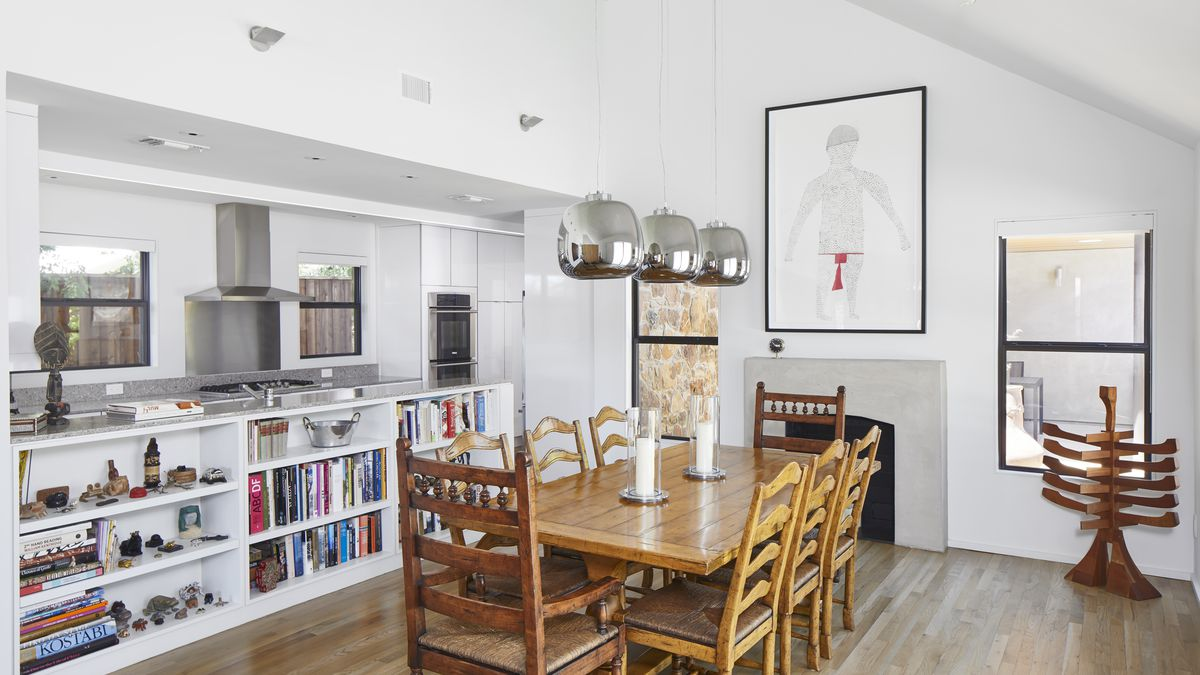 A dining room area with a large wooden table, chairs, and a hardwood floor. There are three metallic light fixtures hanging over the table. A work of art hangs over a fireplace on one wall. There are bookshelves with objects and books behind the table.