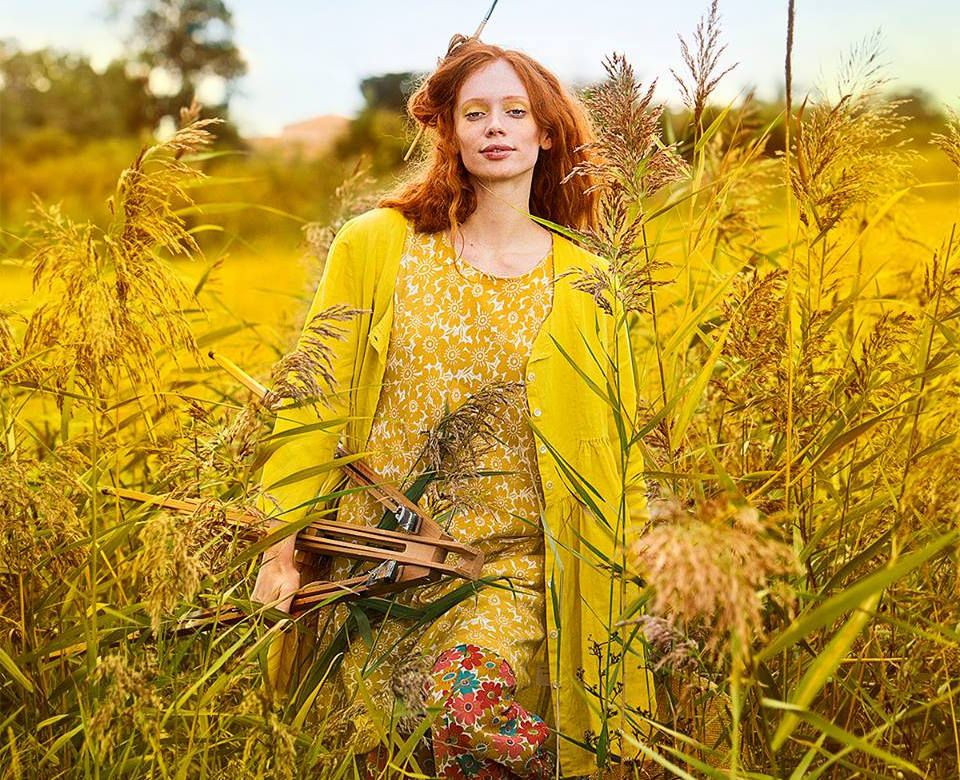 A model wearing a mustard-colored floral dress and pants, in a field