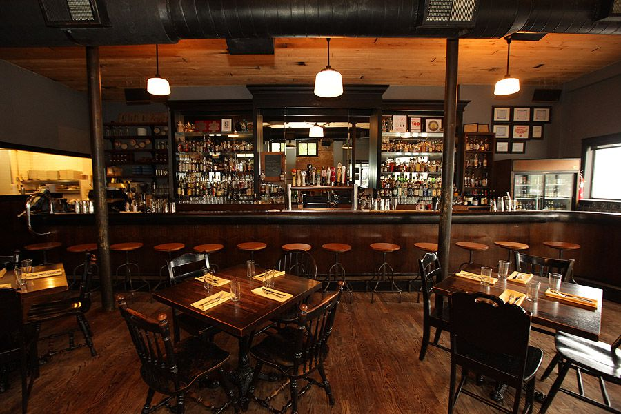 A dark dining room with a large bar filled with bottles