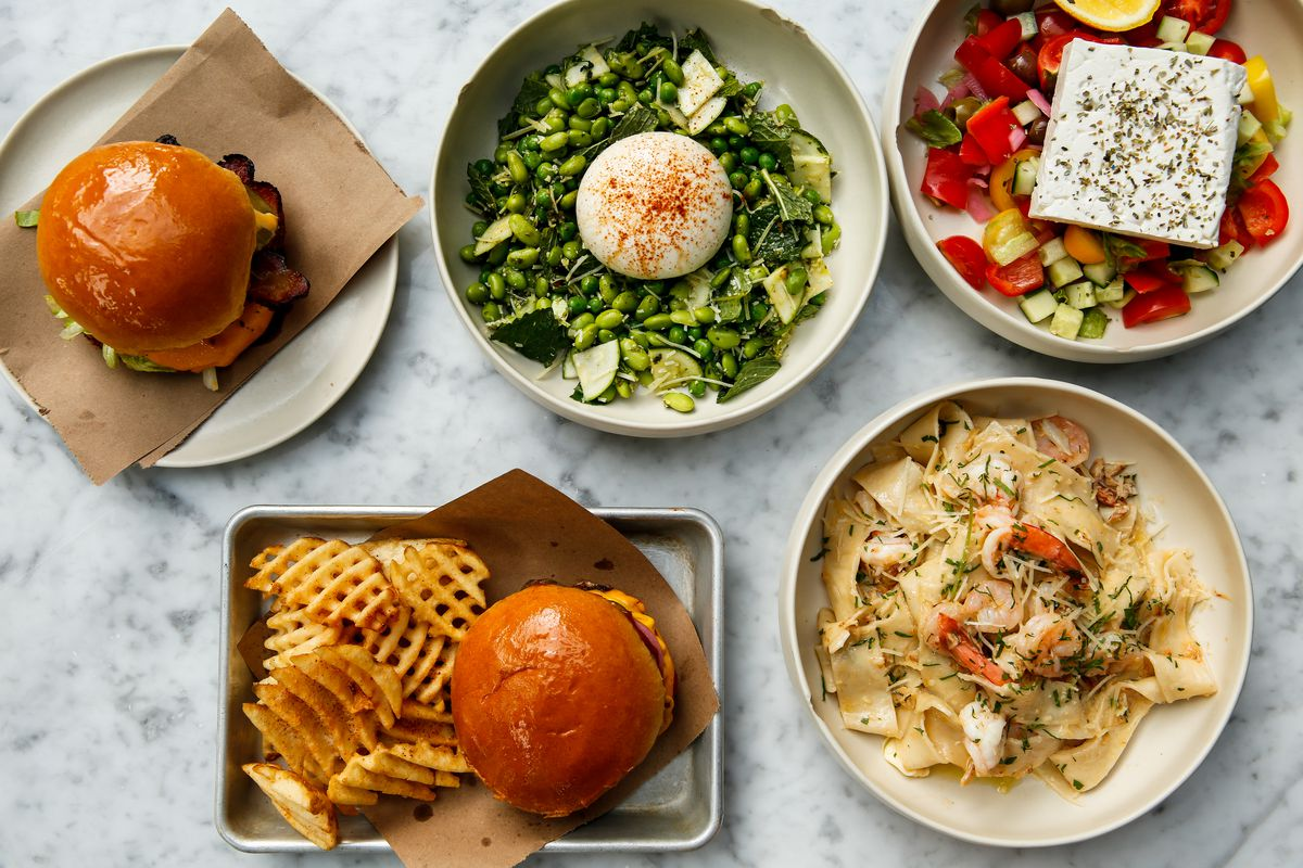 An aerial photograph of five shallow bowls of food, which include dishes like burgers, fried chicken sandwiches, summery salads with bright vegetables, and pasta