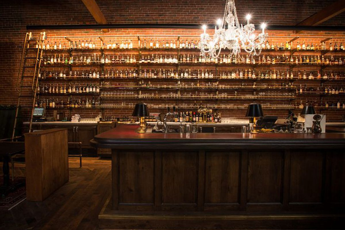 A wall of whiskey lines the bar of the Multnomah Whiskey Library
