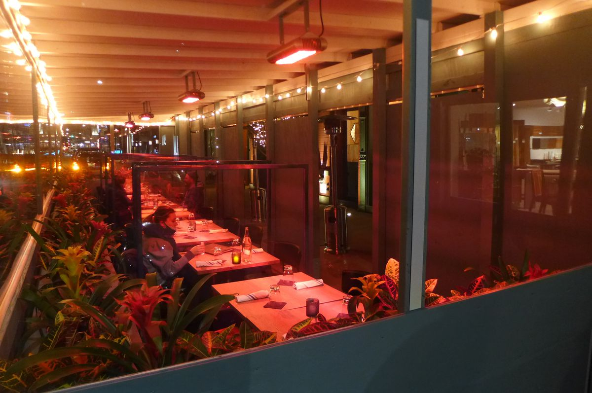 A boxy and yellow tinted space seen through a window with a few diners and heat coils above.