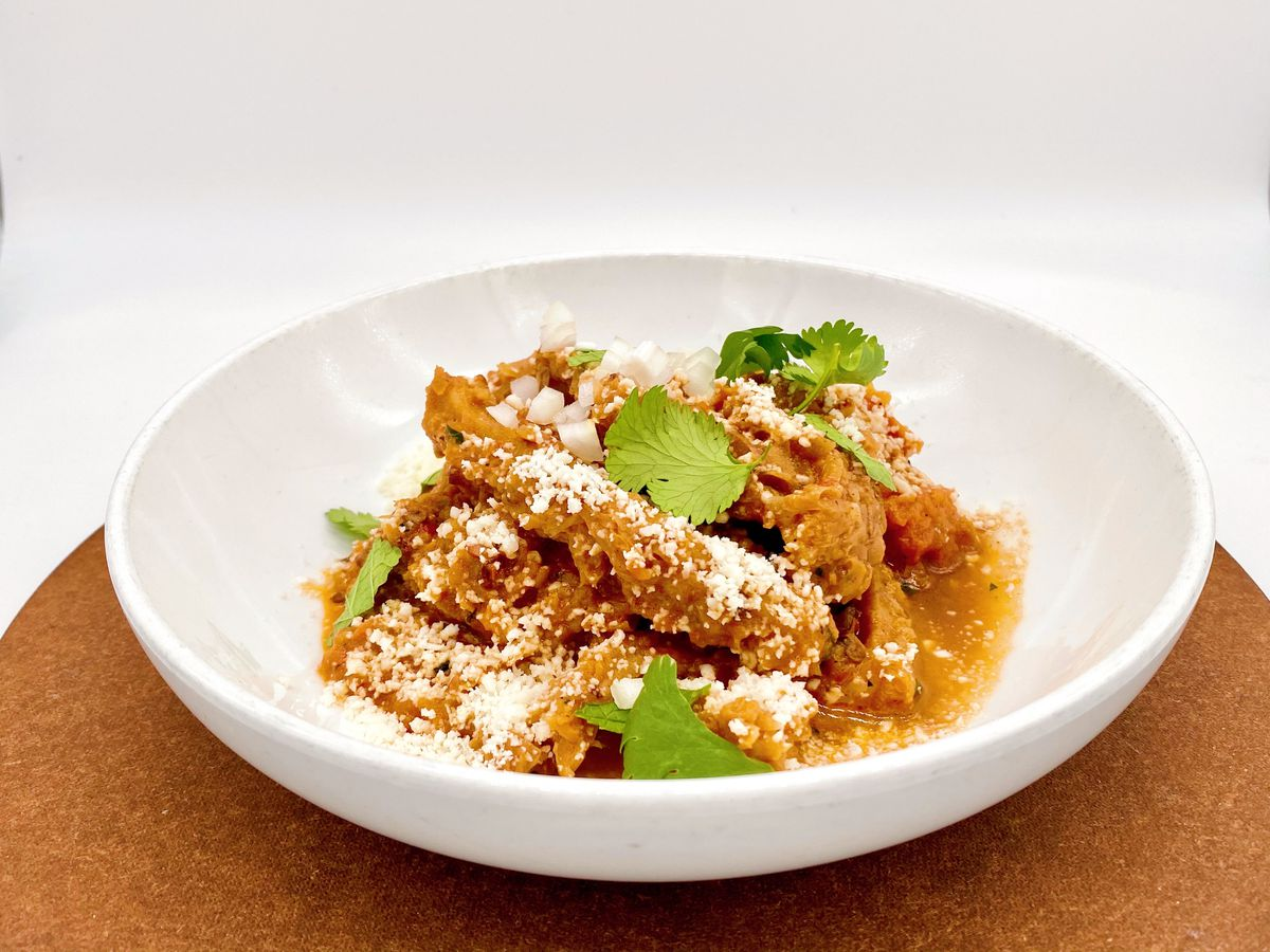 Eight-hour beef tripe, cotija cheese, and chipotle, and cilantro in a white bowl