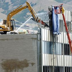 Demolition crews work to bring down a building at 100 South and State Street Friday July 26, 2002.