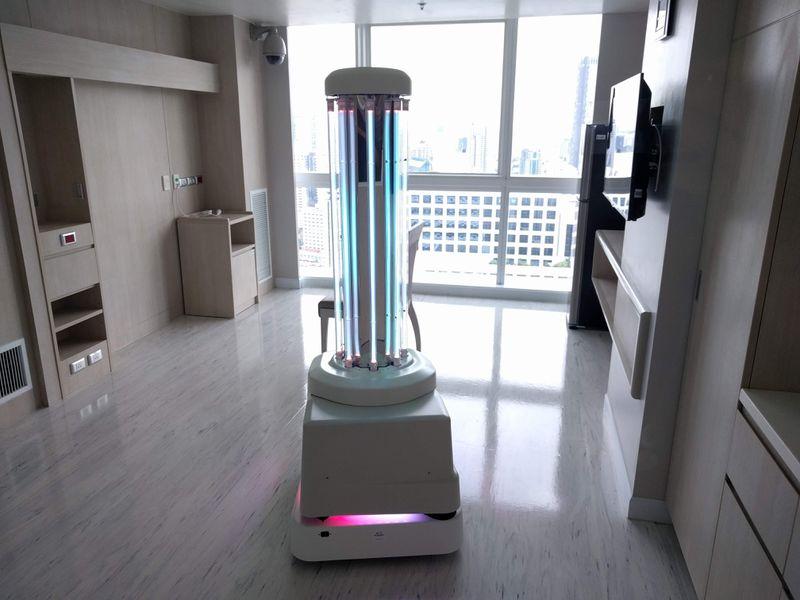 A robot snapped like a light pillar on wheels, parked in a hospital corridor beside a window.