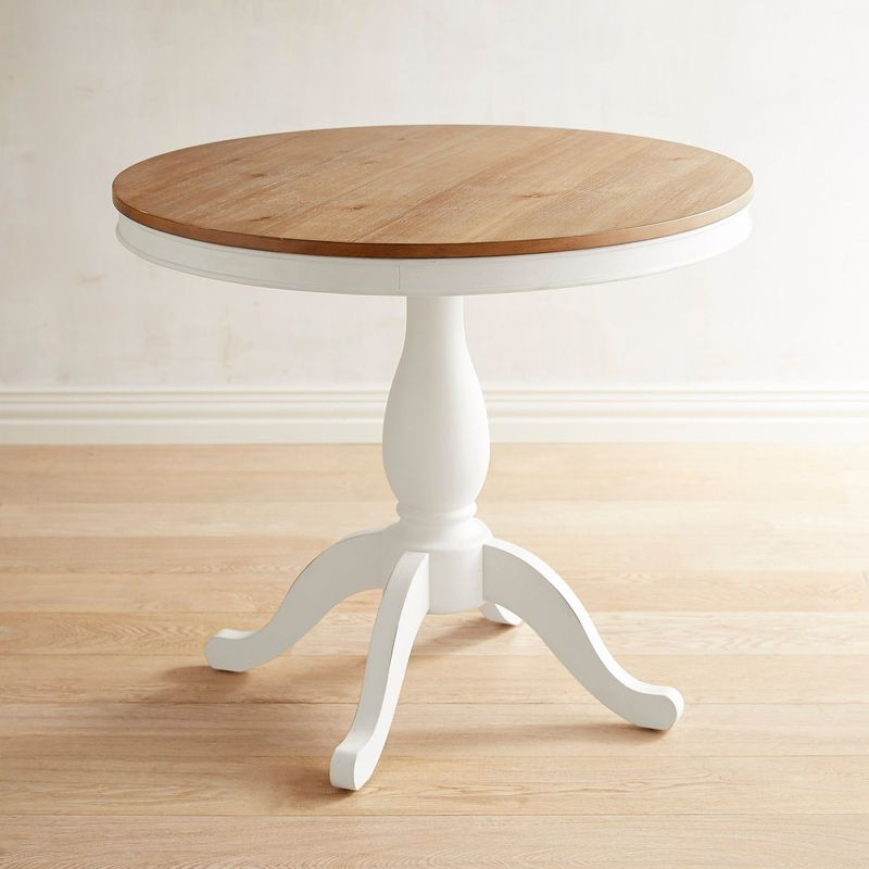 A round table with a natural wood top and white base with four legs.