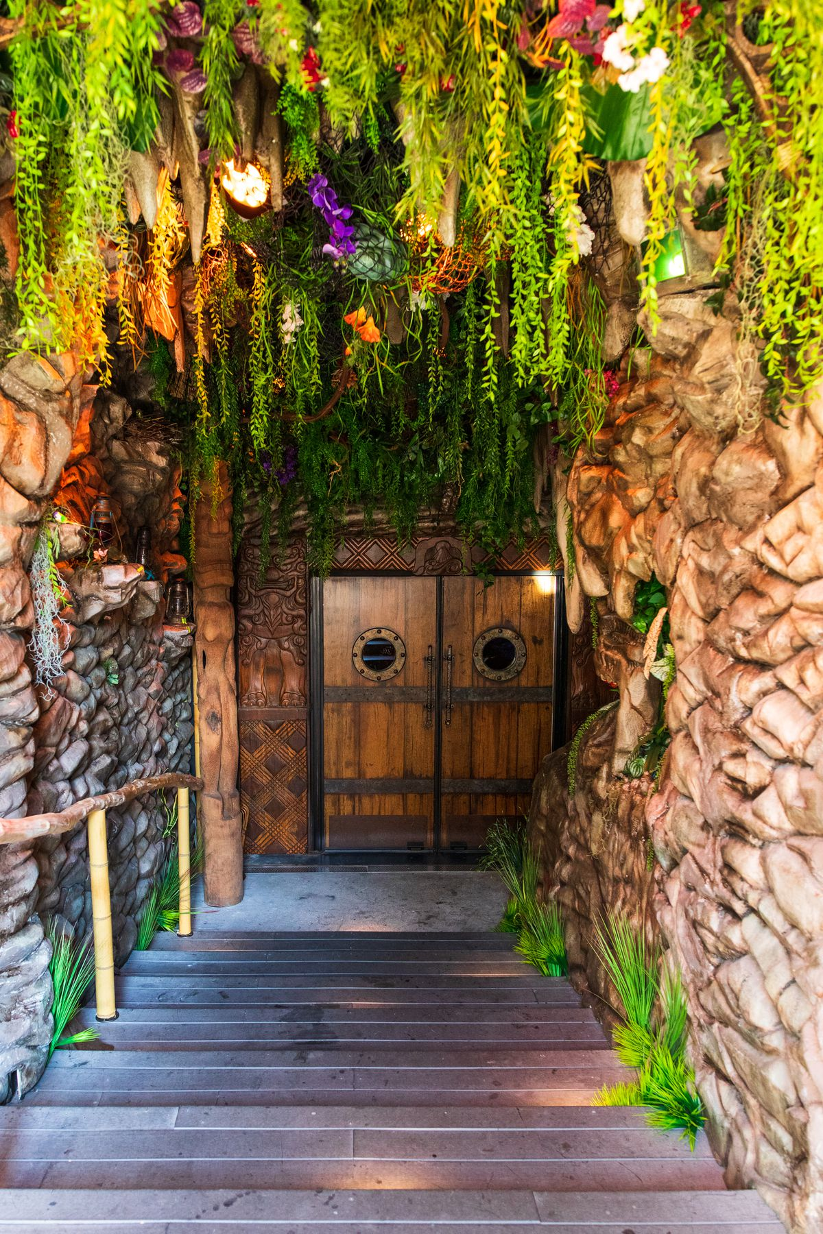 A staircase leads down to double doors with portholes. Overhead, lush green plants and colorful flowers drip from the ceiling