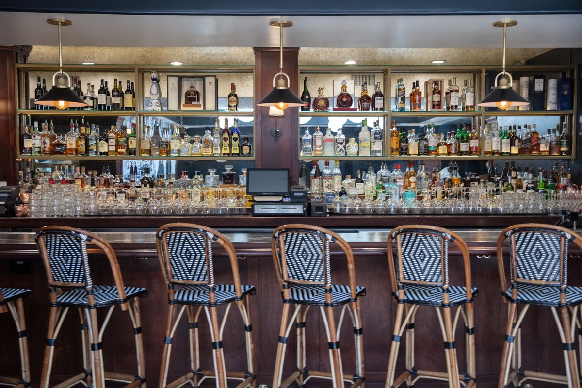 A long bar with turned-out wicker stools.