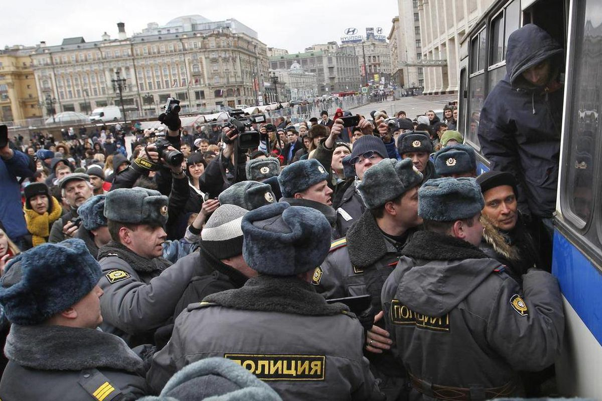 Russian police officers detain protesters during an unsanctioned opposition rally in Moscow, Russia, Sunday, April 1, 2012. Police in Moscow have detained about 30 anti-Kremlin protesters outside the gates to Red Square. Opposition activists called for su
