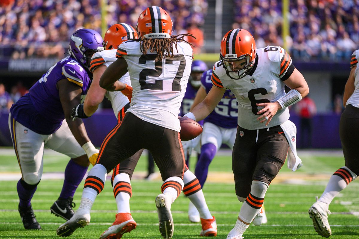 Baker Mayfield #6 of the Cleveland Browns fakes a handoff to Kareem Hunt #27 in the fourth quarter of the game against the Minnesota Vikings at U.S. Bank Stadium on October 3, 2021 in Minneapolis, Minnesota.