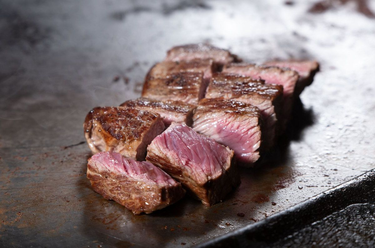A piece of sliced steak on a griddle.