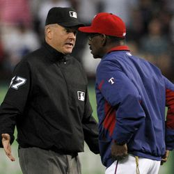 Second base umpire Mike Everitt responds to an inquiry from Texas Rangers manger Ron Washington, right, on a Ian Kinsler hit that put him on second in the first inning of a baseball game against the Seattle Mariners Friday, Sept. 14, 2012, in Arlington, Texas. After officials reviewed the hit on video it was ruled a home run.