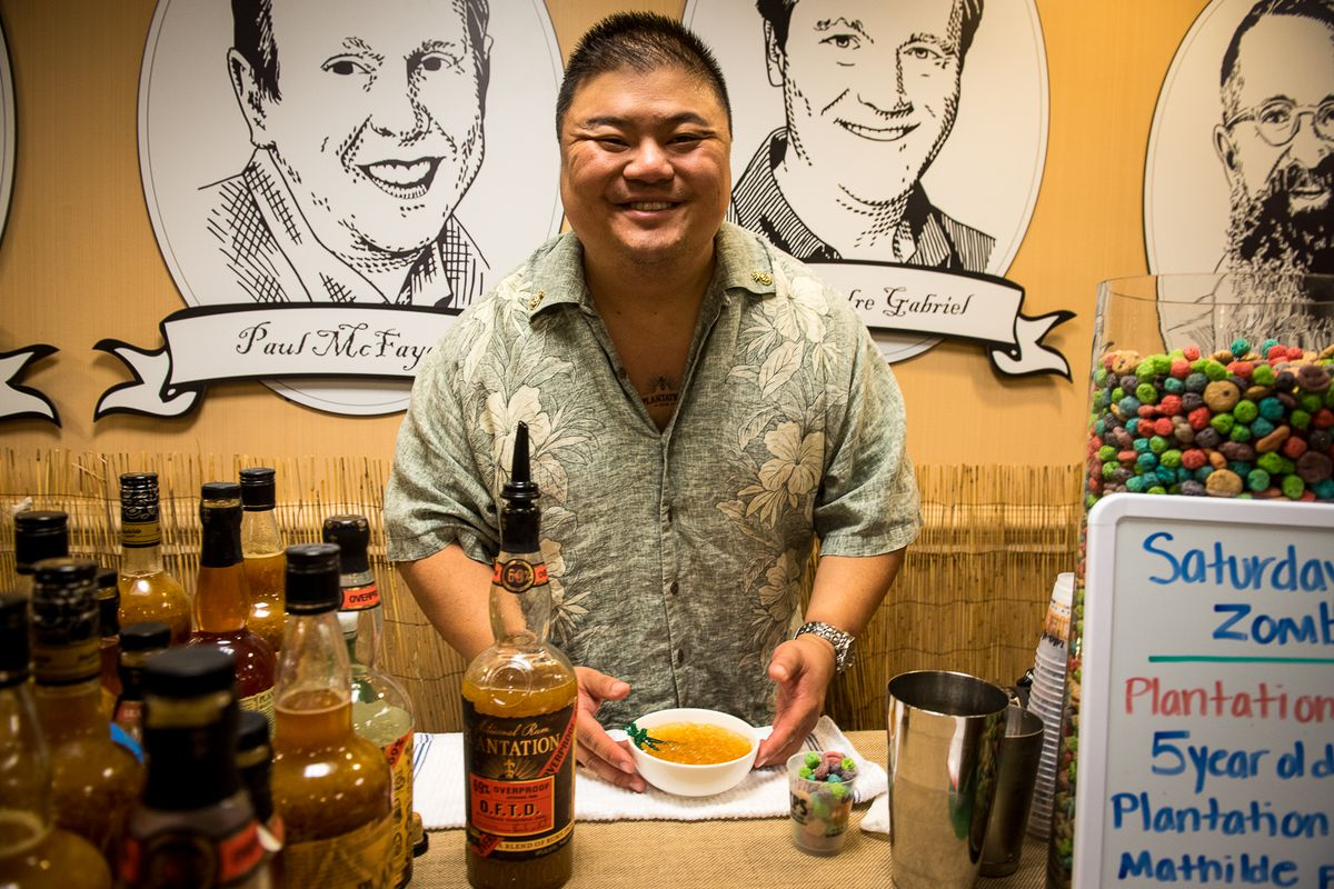 A photo of Rocky Yeh in a Hawaiian shirt, smiling at a table with various liquor bottles.