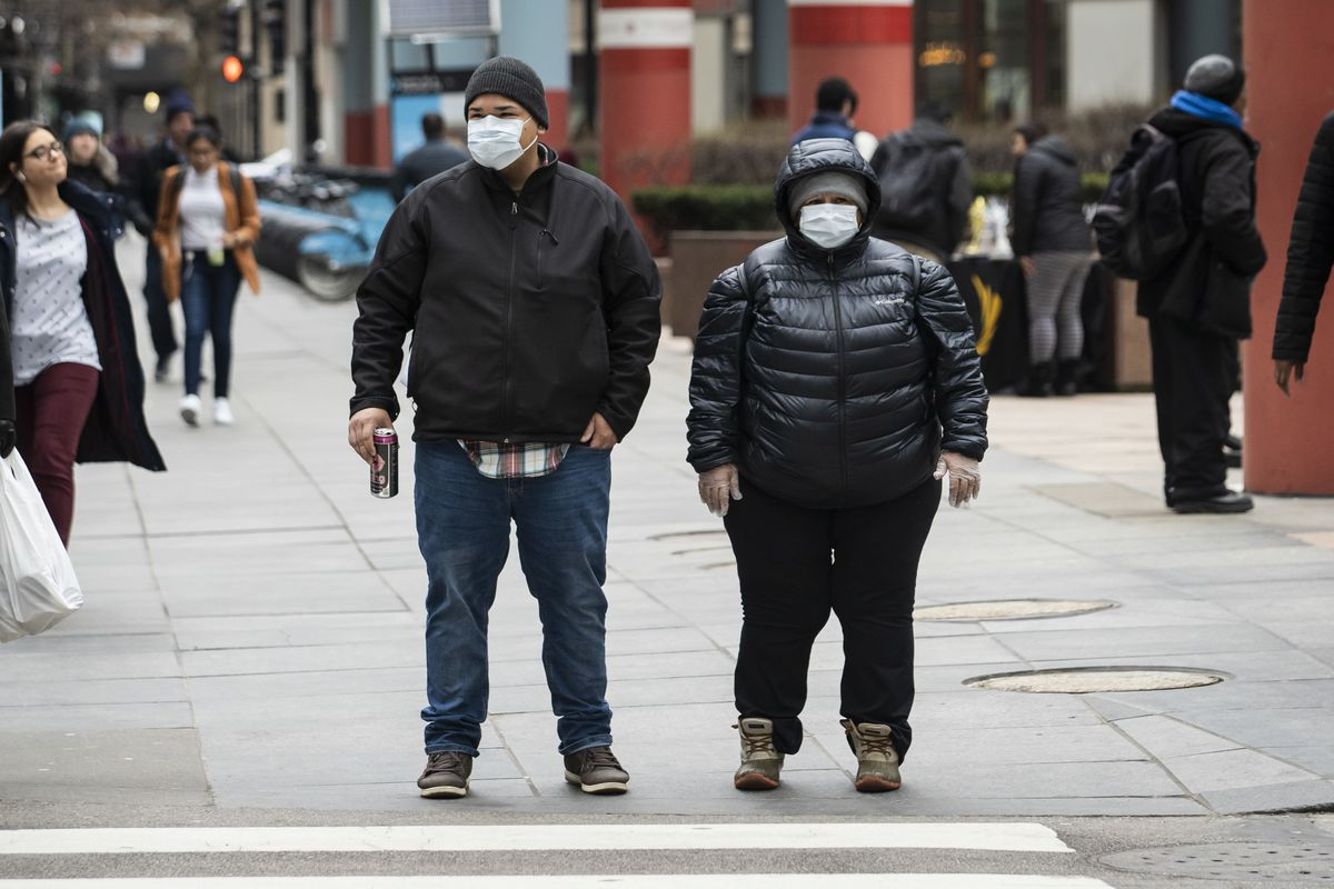 A man and woman in the Loop wear face masks Thursday amid growing fear about the coronavirus.