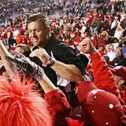 Utah coach Kyle Whittingham is hoisted on the shoulders of players and fans as the Utes escape with a 41-34 overtime win in Provo Saturday.
